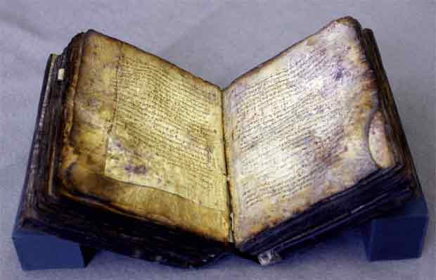 The codex Archimedes Palimpsest: book opened to middle with darkened, spotty pages and worn blackened edges